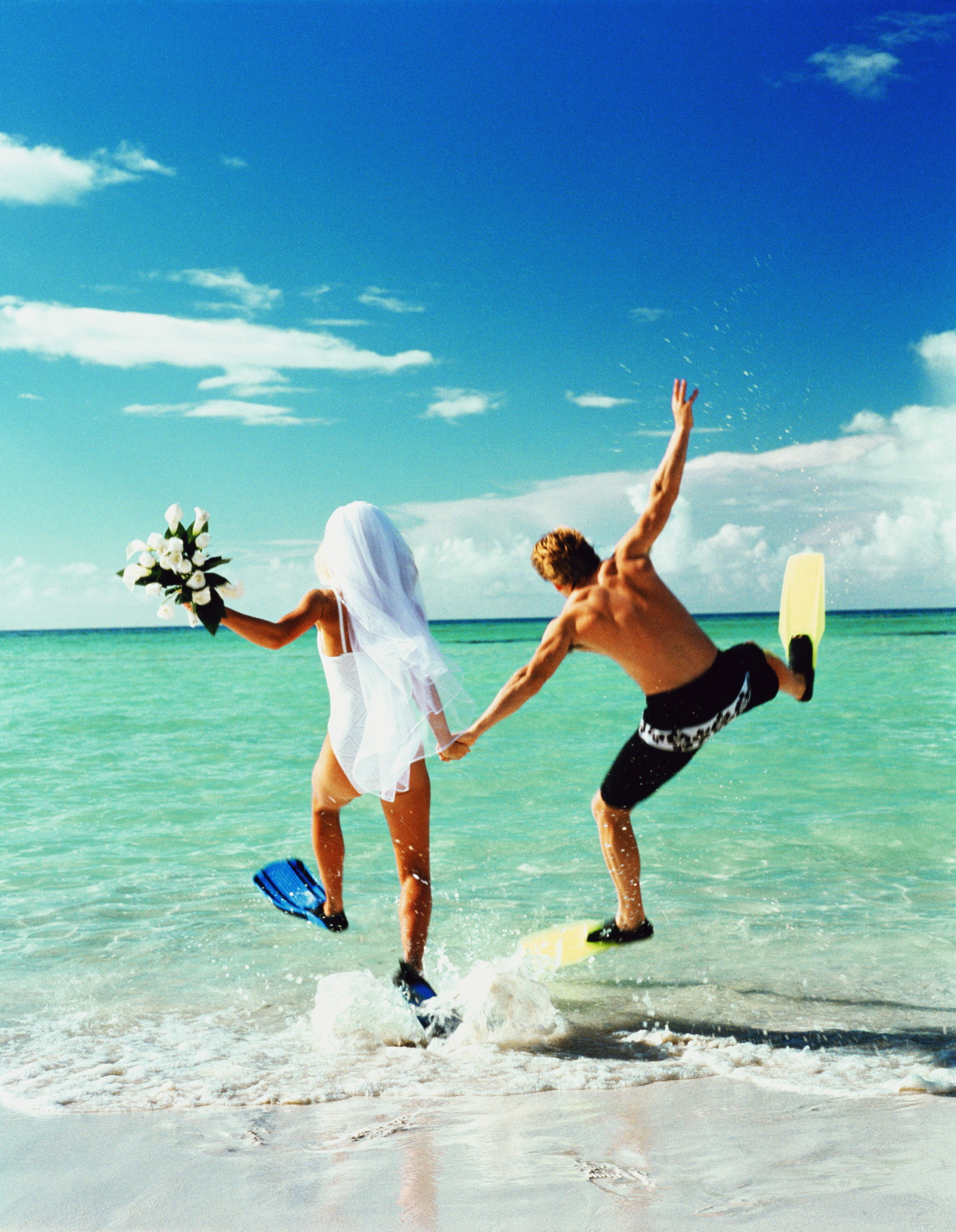Bride and groom wearing flippers, running into ocean